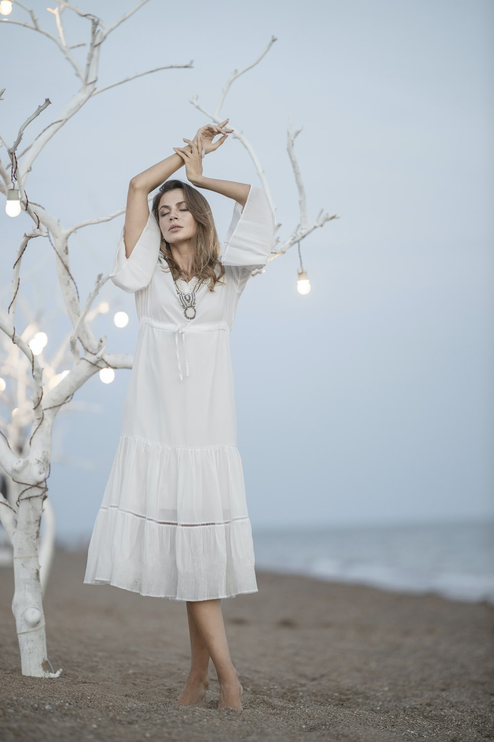 woman in white dress standing on white tree branch during daytime