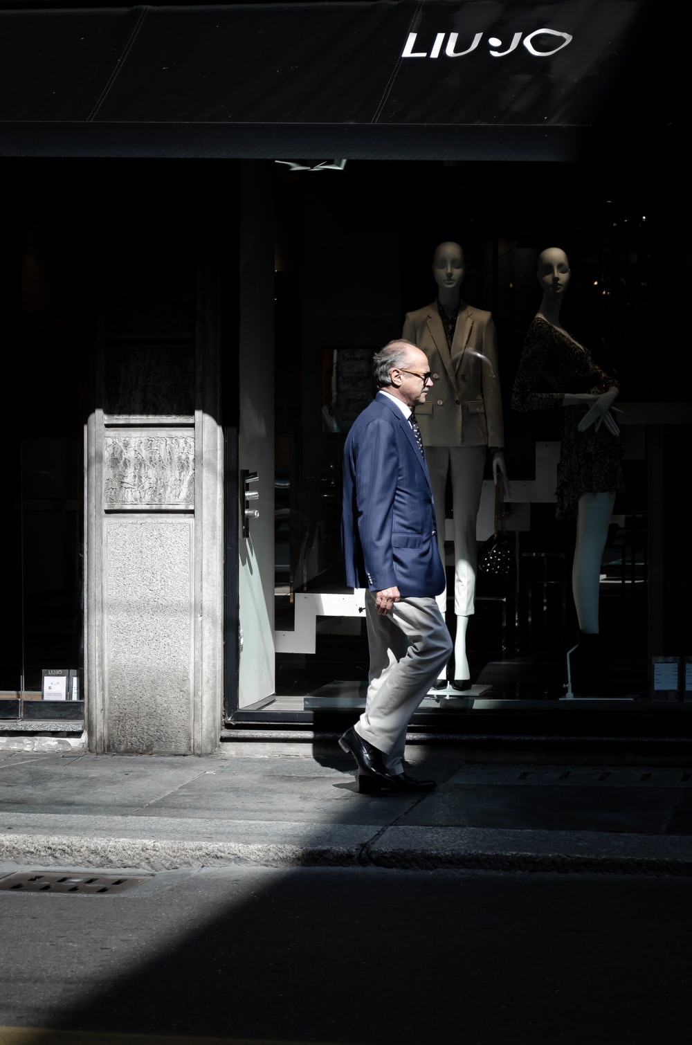 man in blue button up shirt and white pants walking on sidewalk during daytime