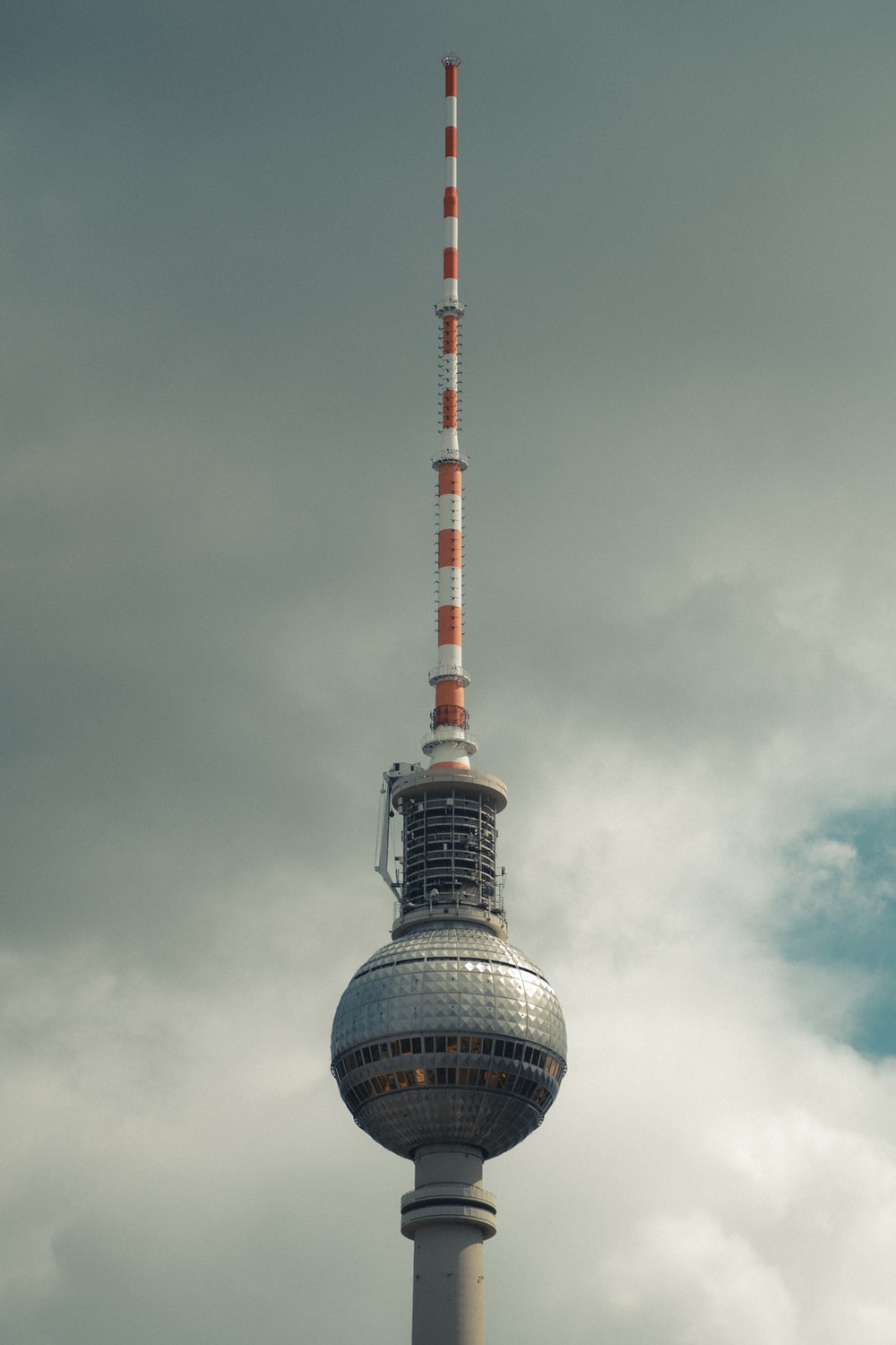 white and red tower under cloudy sky