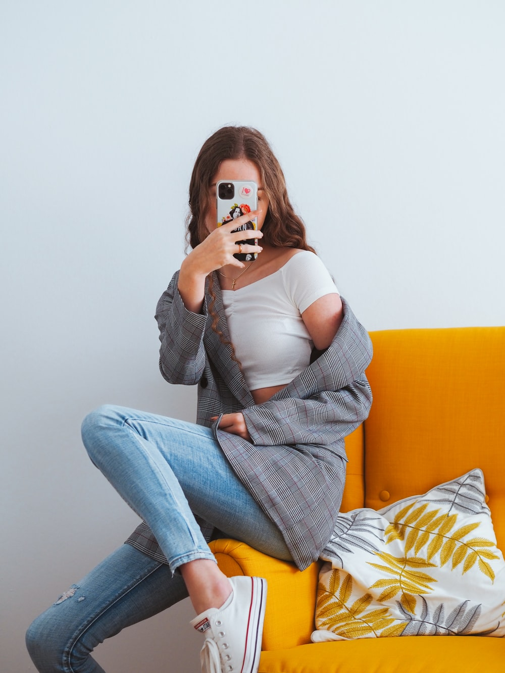 woman in gray cardigan and blue denim jeans sitting on yellow couch