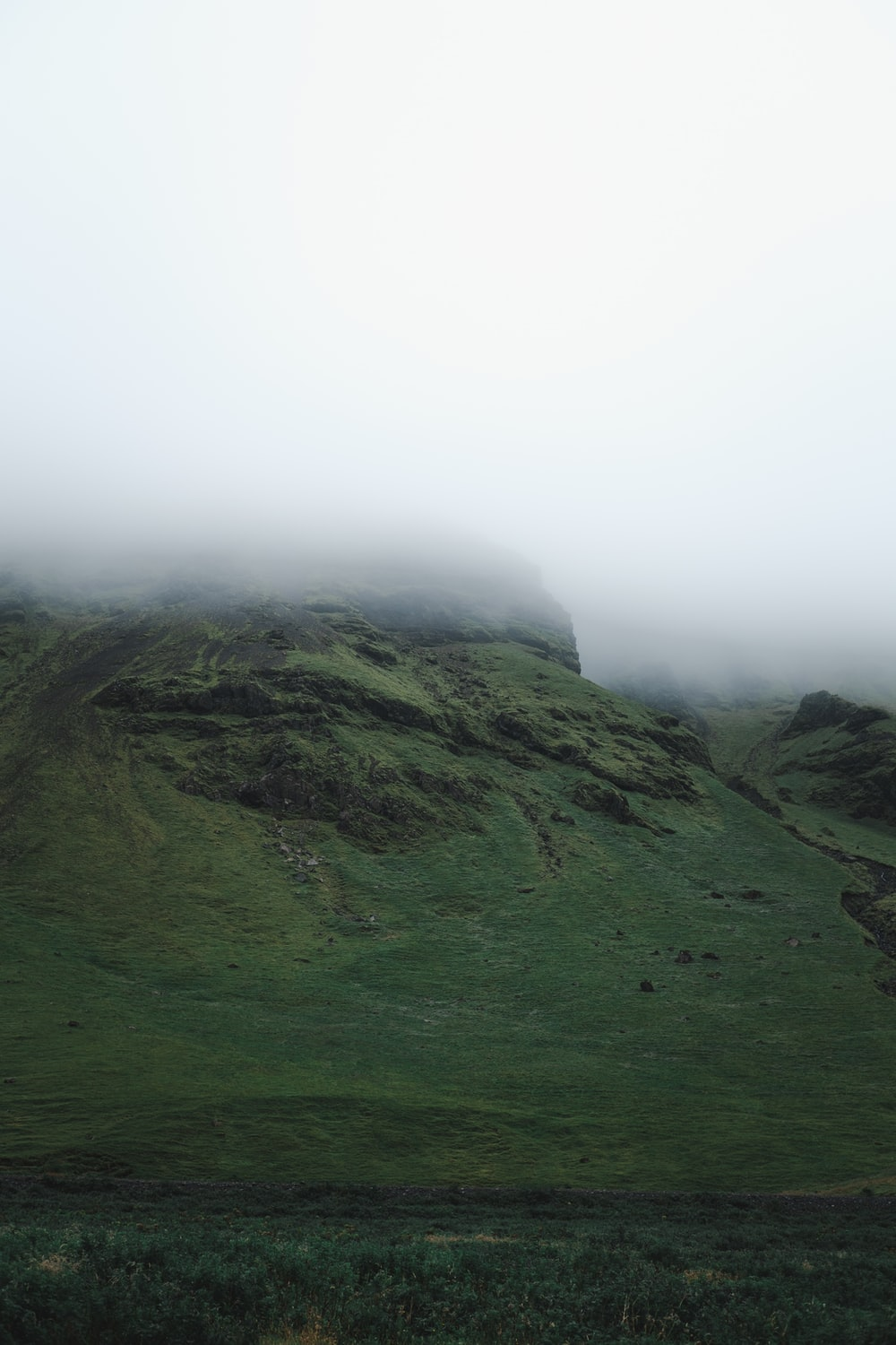 green grass covered mountain under white sky during daytime