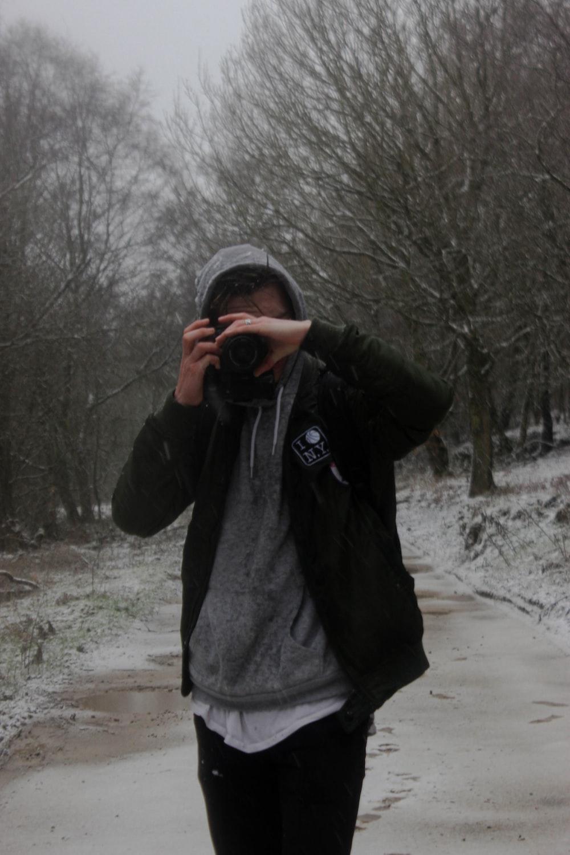 man in black jacket taking photo of bare trees during daytime
