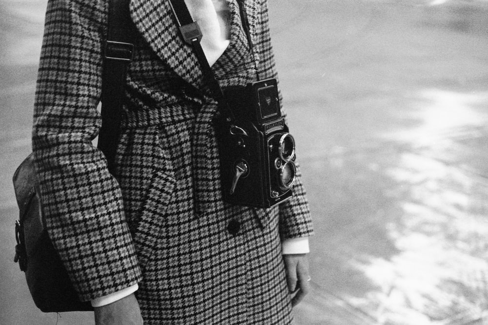 grayscale photo of woman in black and white checkered coat