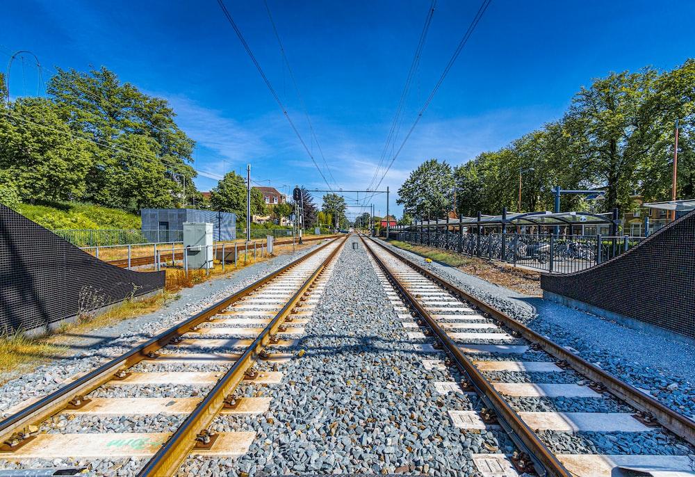 train rail tracks near green trees during daytime