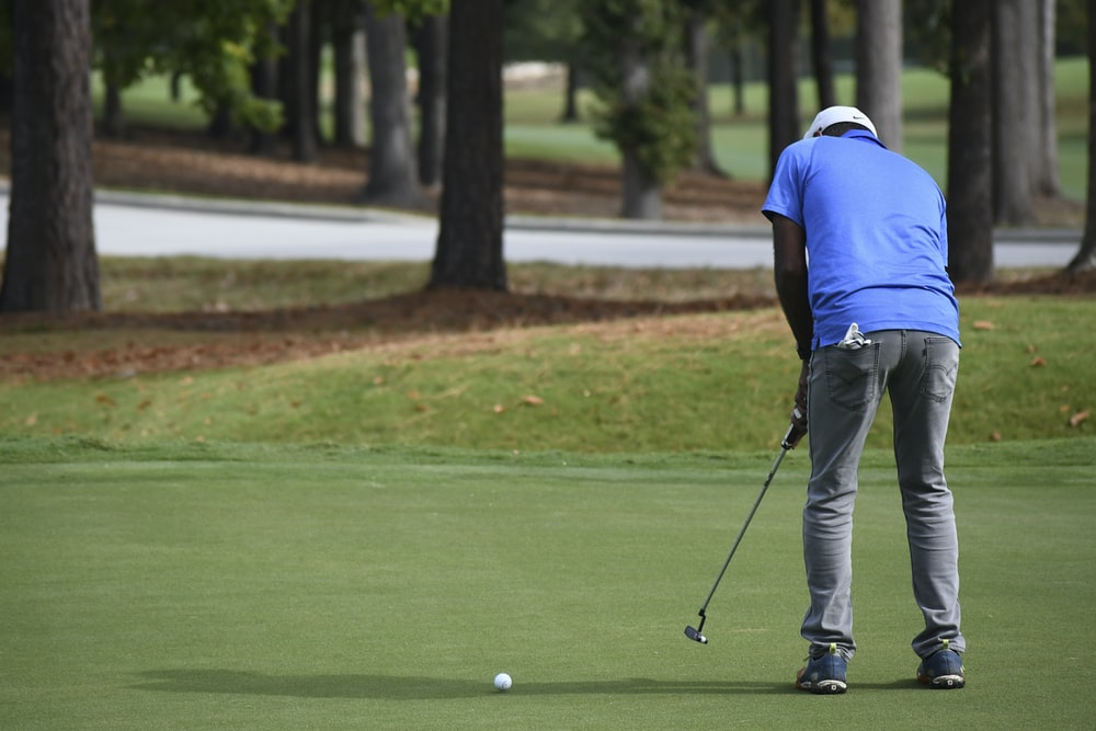 man in blue polo shirt and gray pants playing golf during daytime