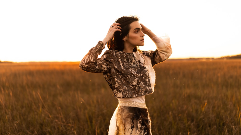 woman in white and black floral long sleeve dress standing on grass field