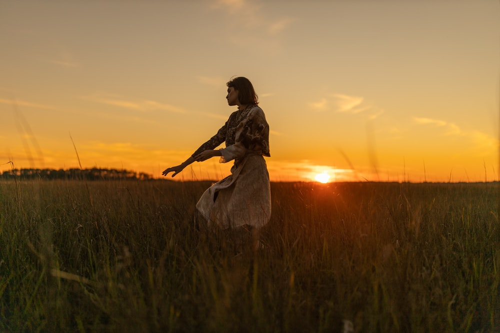 woman in white dress standing on green grass field during sunset