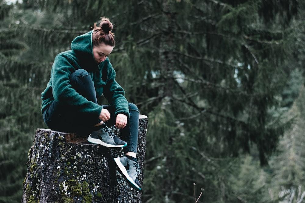 woman in green jacket sitting on tree log