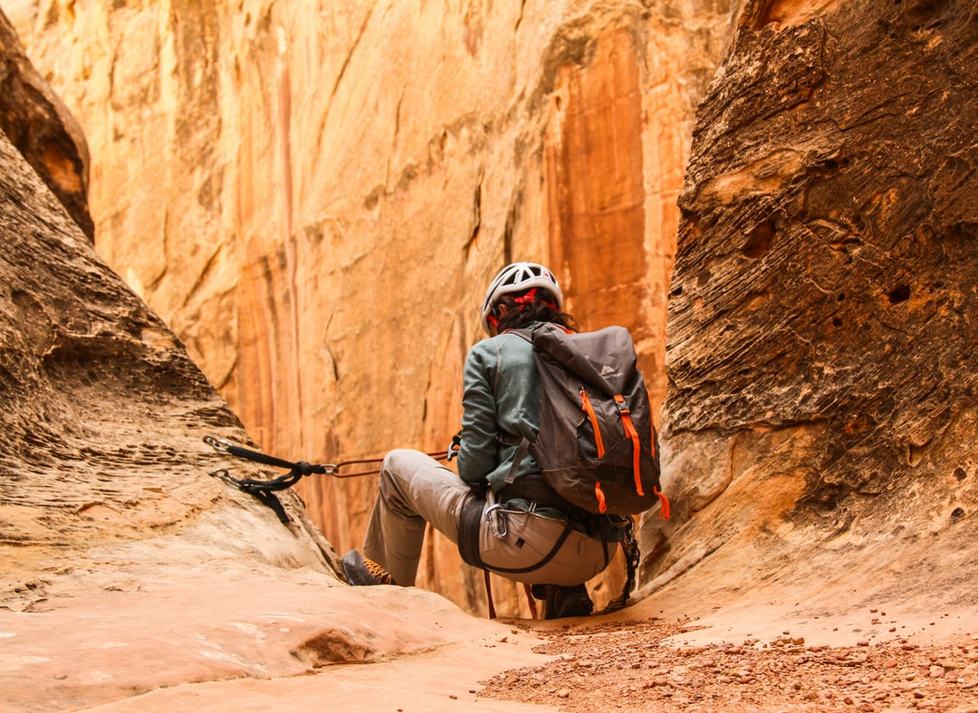 Man In Gray Jacket and Black Helmet Sitting On Brown Rock Formation During Daytime - unsplash