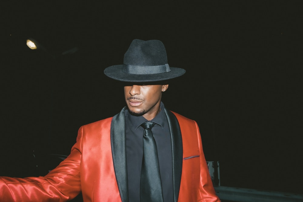 man in black hat and red blazer
