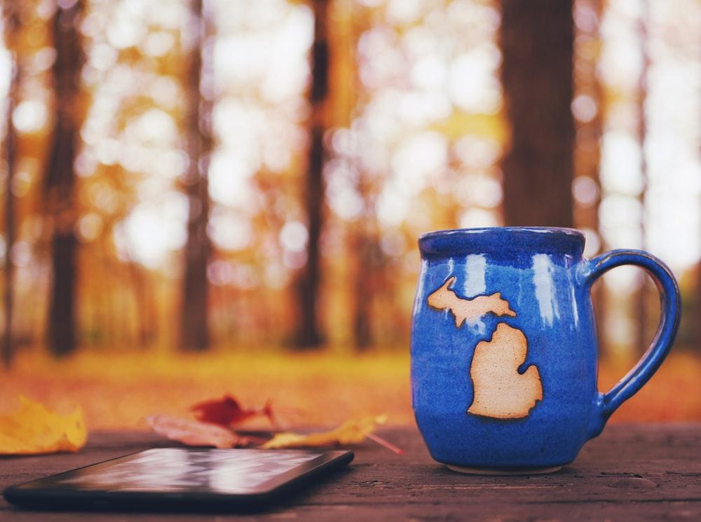 blue ceramic vase on brown wooden table