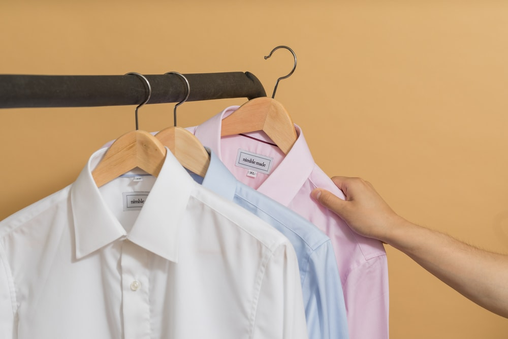 white button up shirt on brown clothes hanger