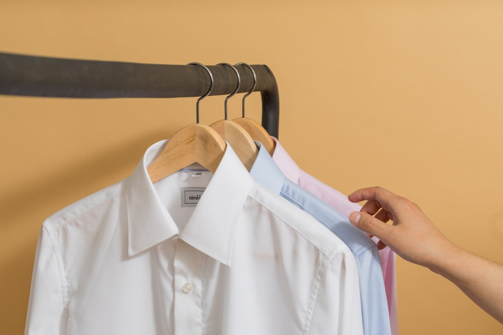 white button up shirt on black clothes hanger