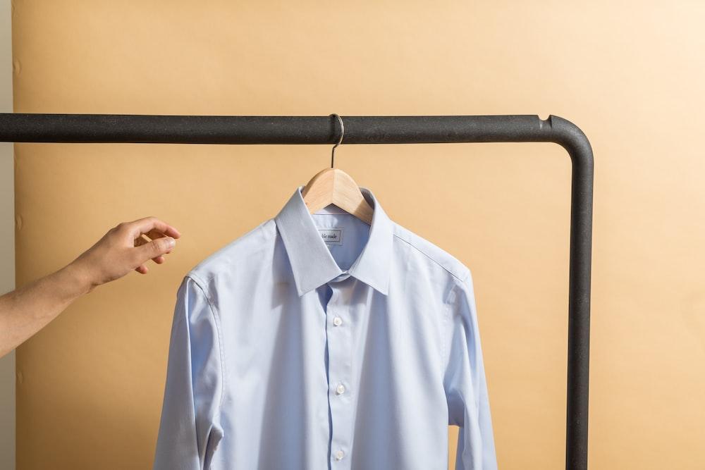 white button up shirt hanging on black metal bar
