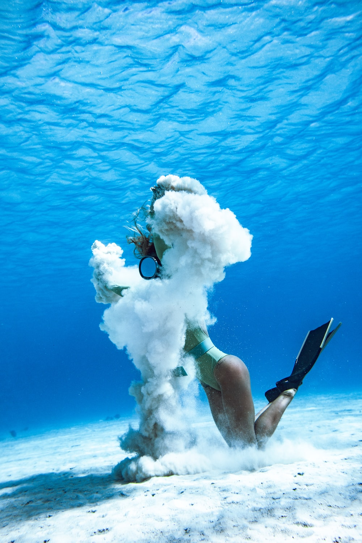 woman in black and blue bikini set holding white smoke