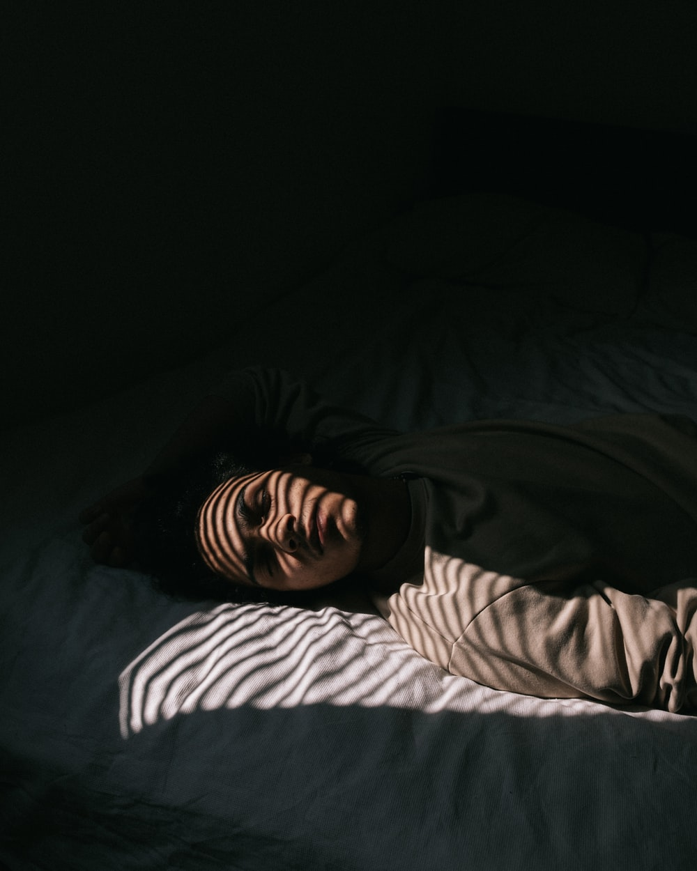 man in black and white striped long sleeve shirt lying on bed