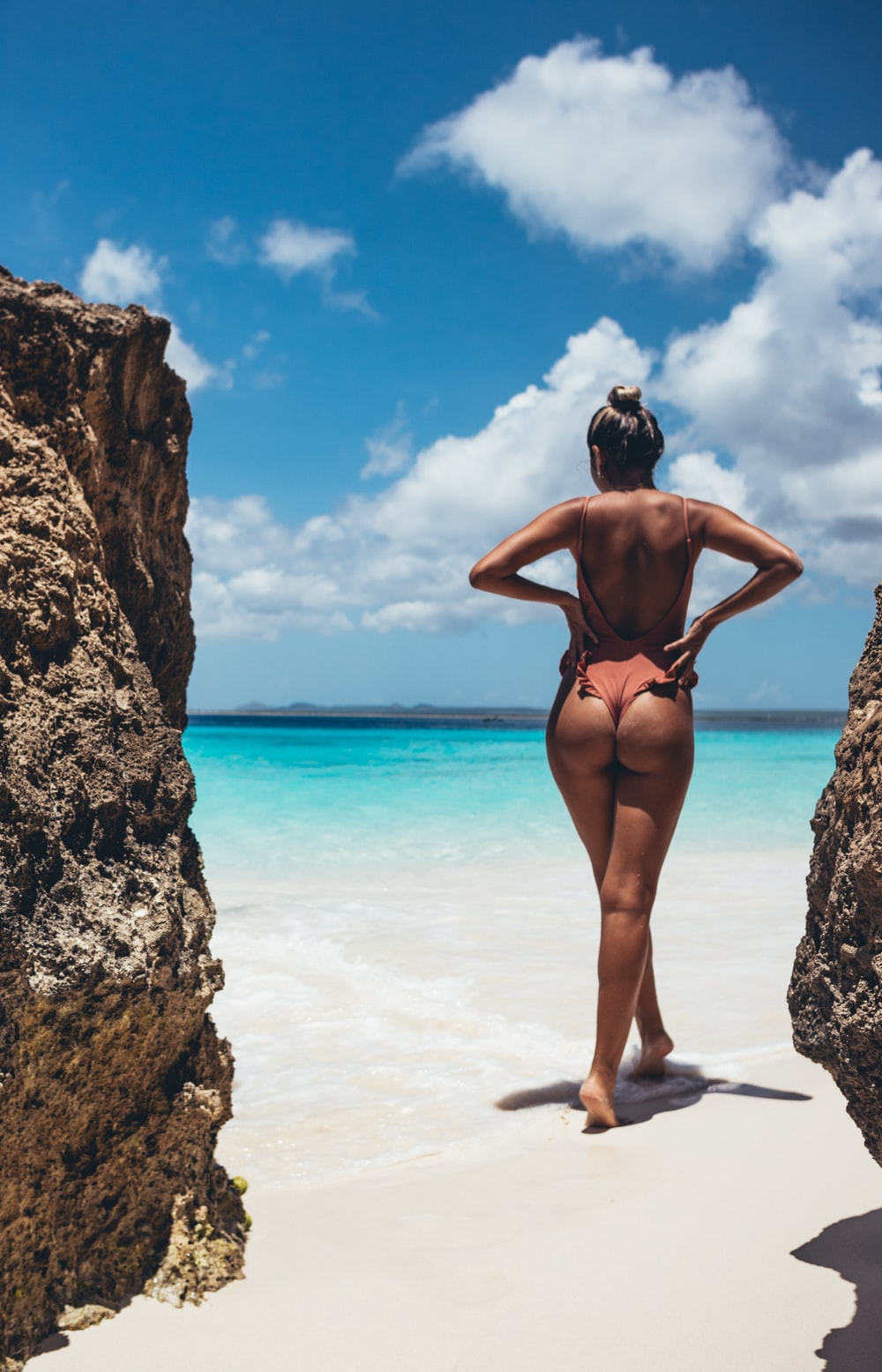 woman in black bikini standing on beach during daytime