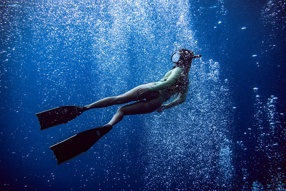 woman in black one piece swimsuit under water