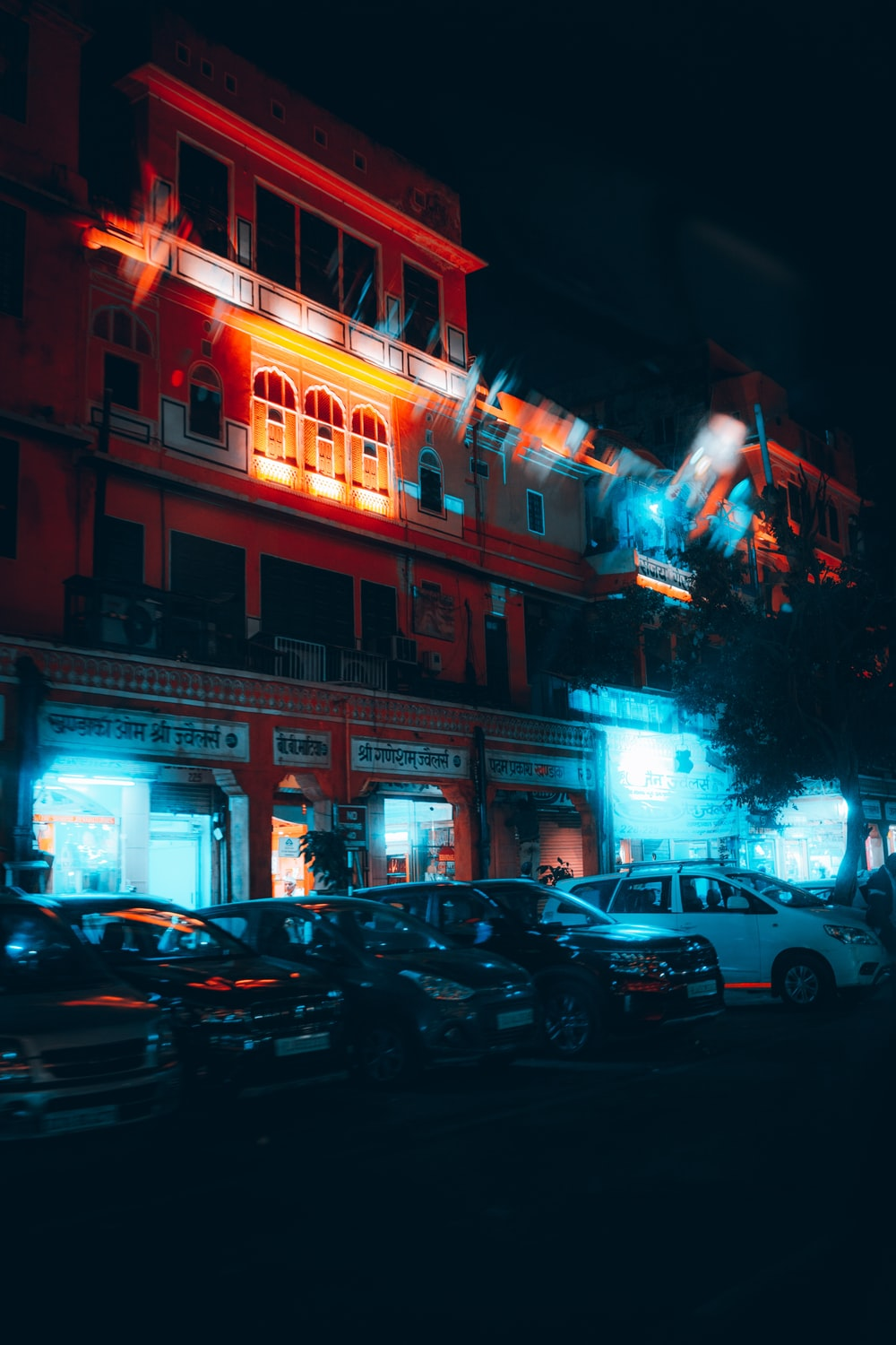cars parked in front of red building during night time