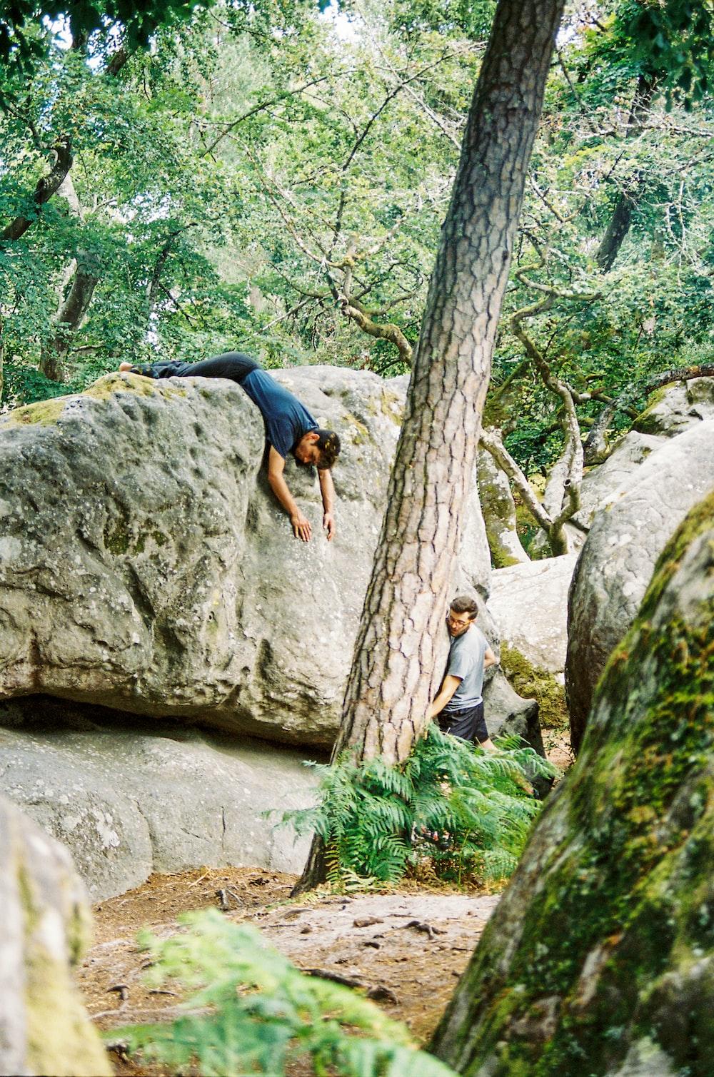 woman in black t-shirt climbing on brown rock