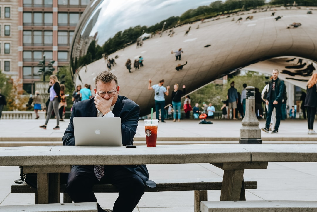 Man In Black Jacket Sitting On Chair In Front of Macbook - unsplash