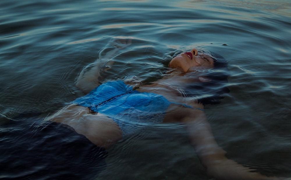 woman in blue bikini lying on water