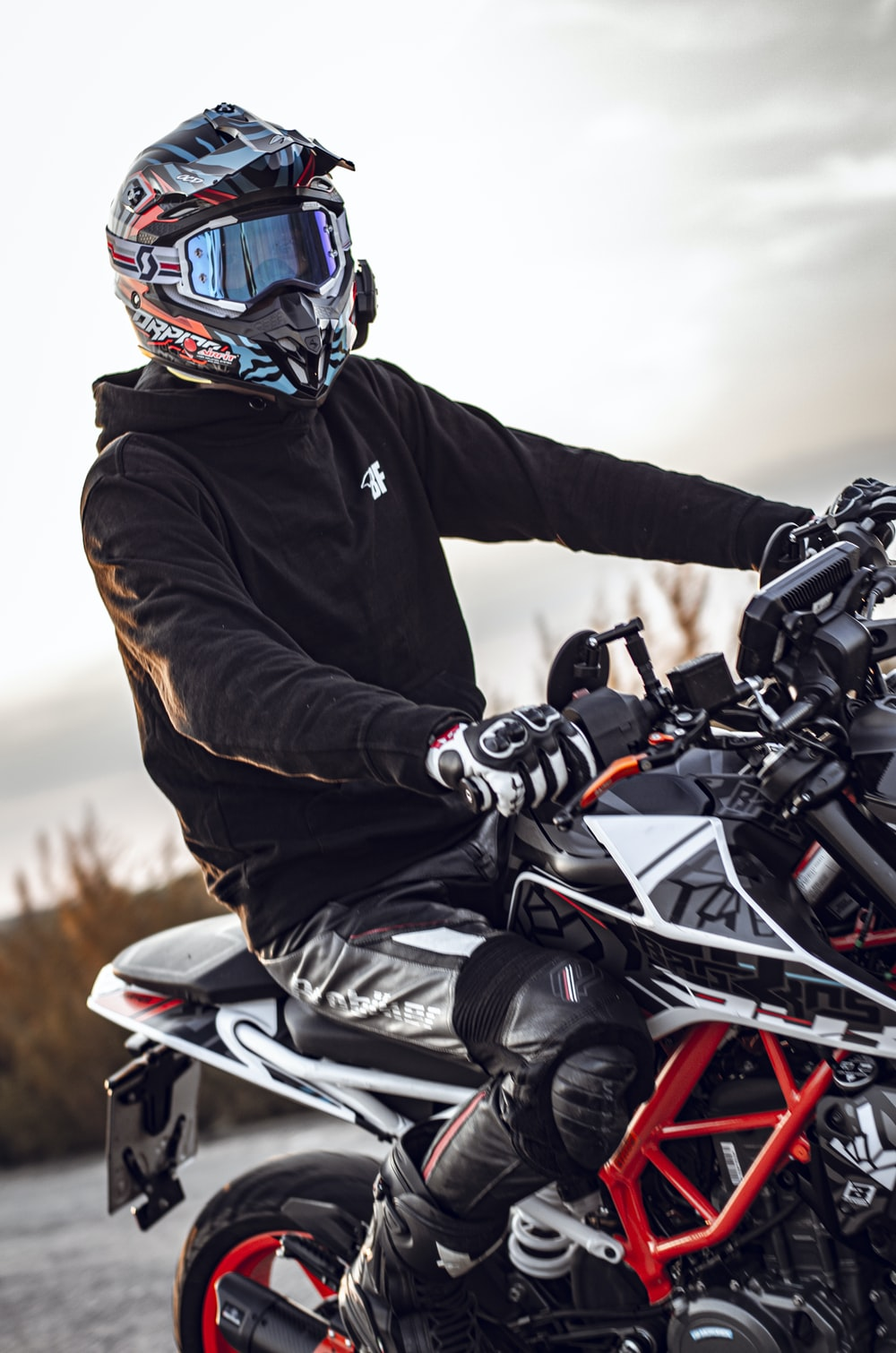 man in black jacket riding white and black sports bike