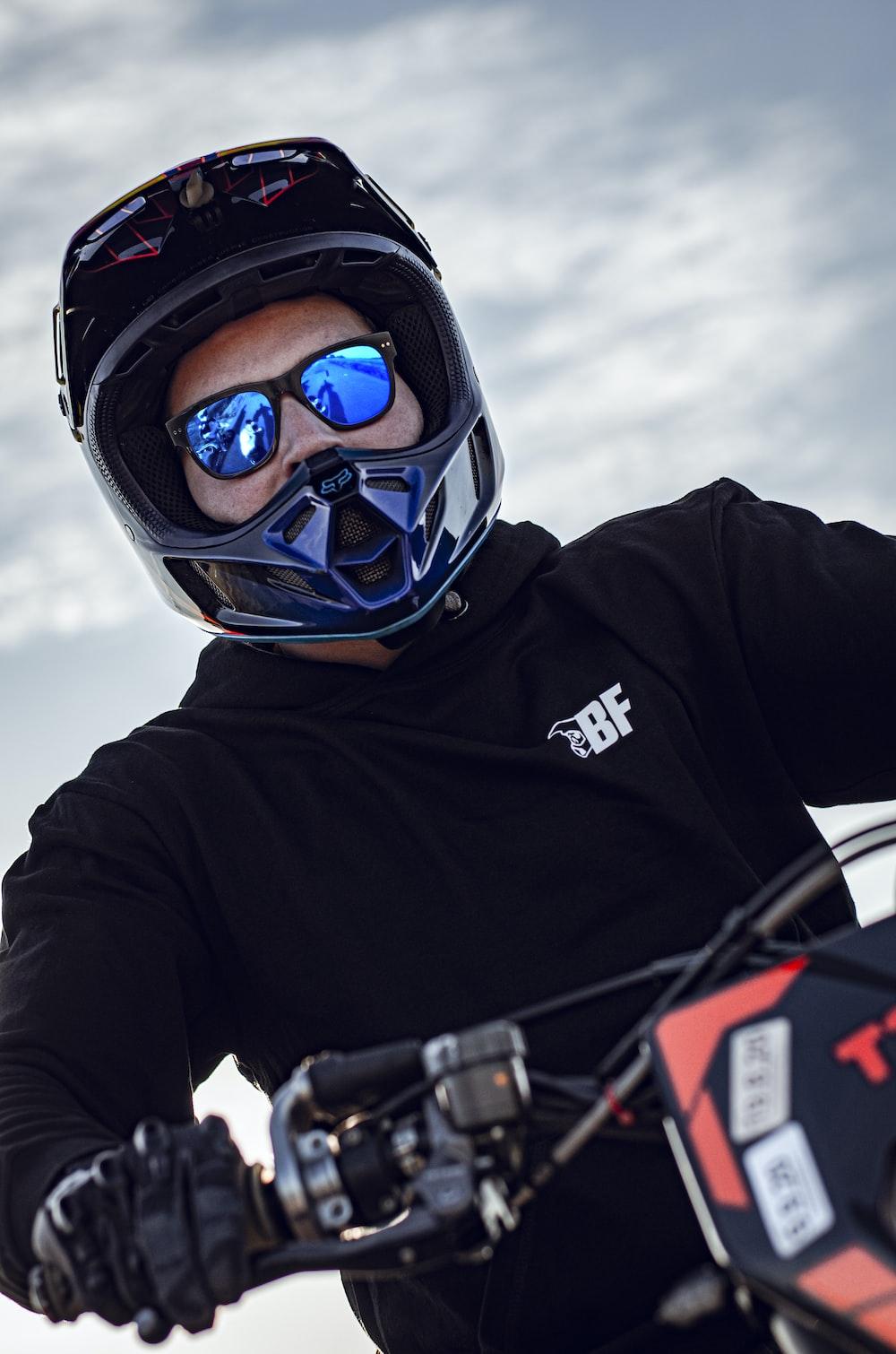 man in black jacket wearing blue helmet and black goggles