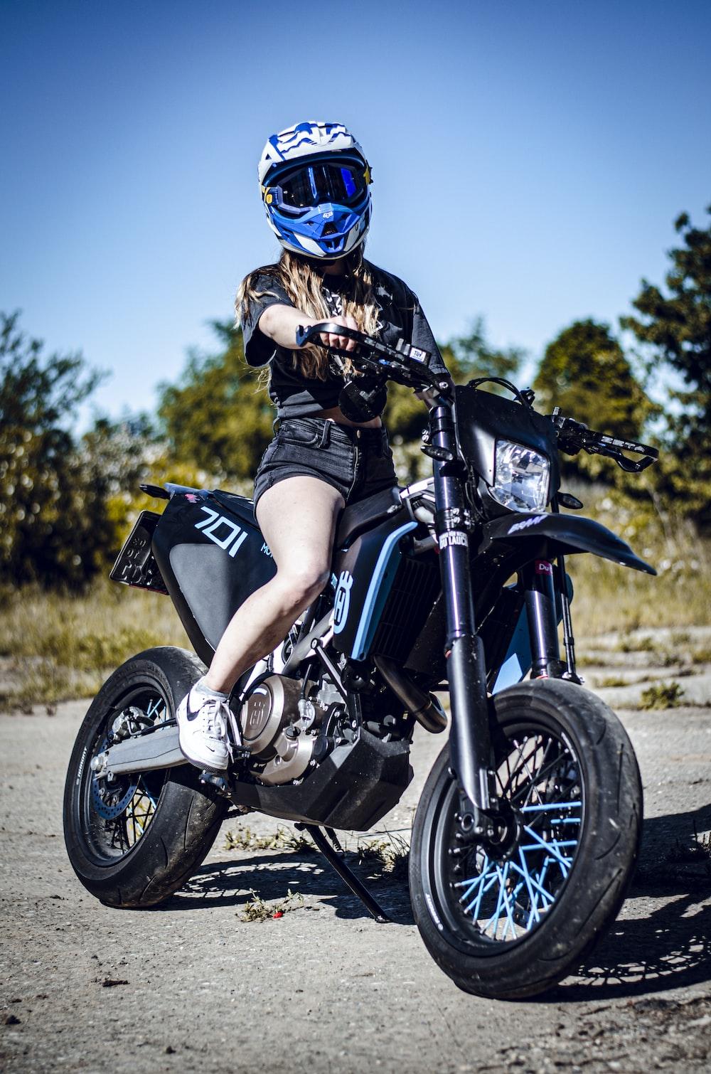 man in blue helmet riding black motorcycle