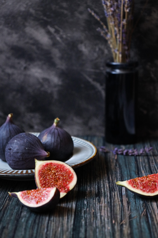 sliced tomato on white ceramic plate beside black bottle