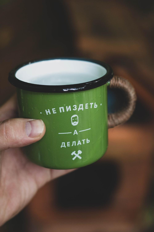 green and black ceramic mug with coffee