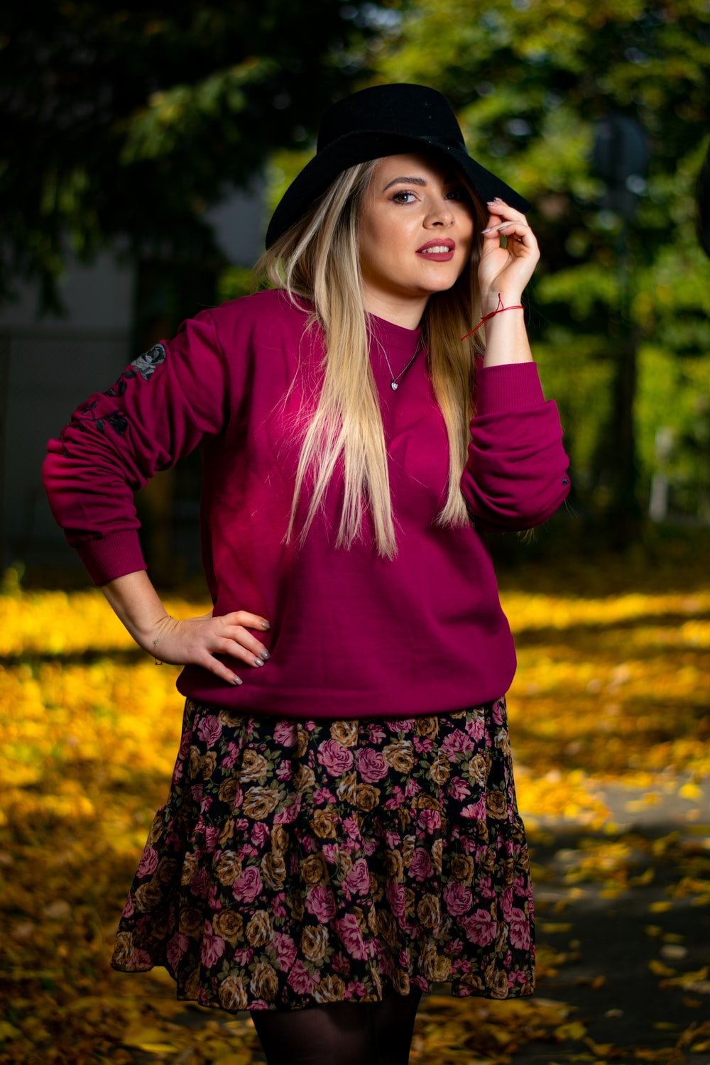 woman in purple long sleeve shirt and black and pink floral skirt