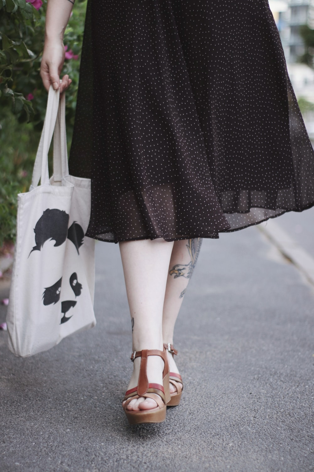 woman in black and white dress holding white tote bag