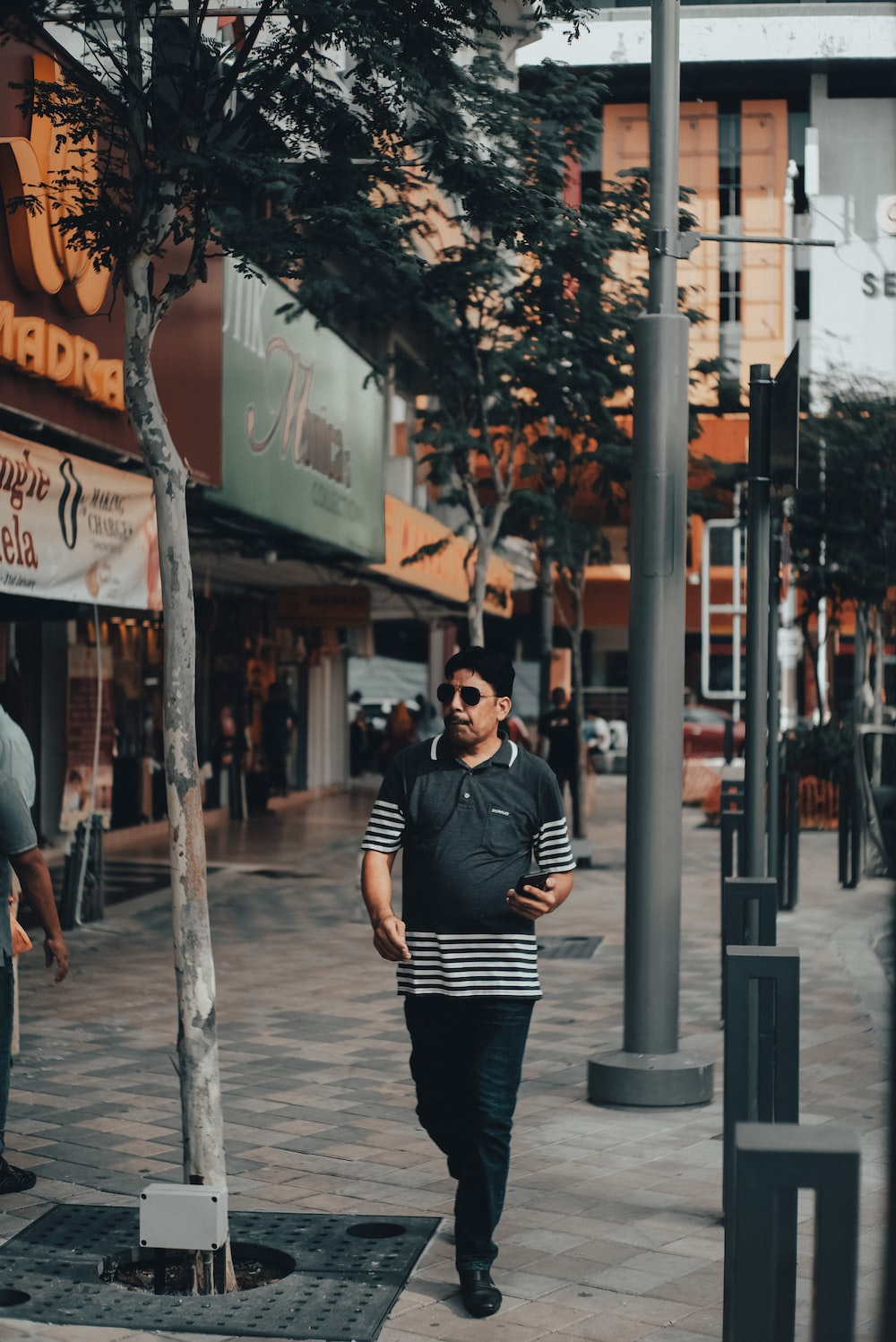 man in black and white striped long sleeve shirt and black pants standing on sidewalk during