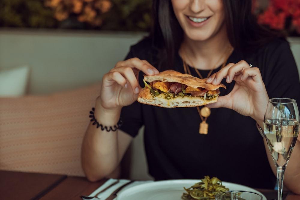 woman in black long sleeve shirt holding a burger