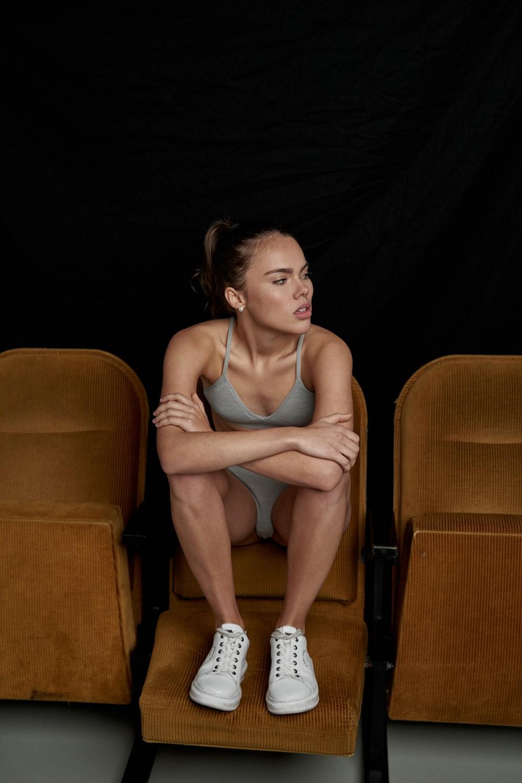 woman in gray tank top sitting on brown sofa chair