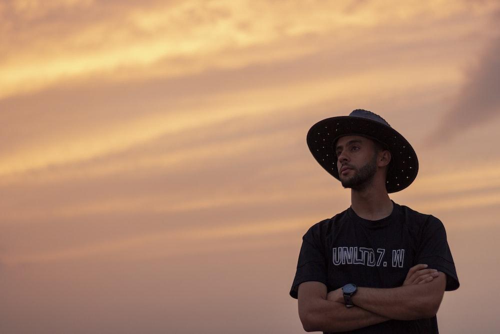 man in black cowboy hat and black crew neck t-shirt