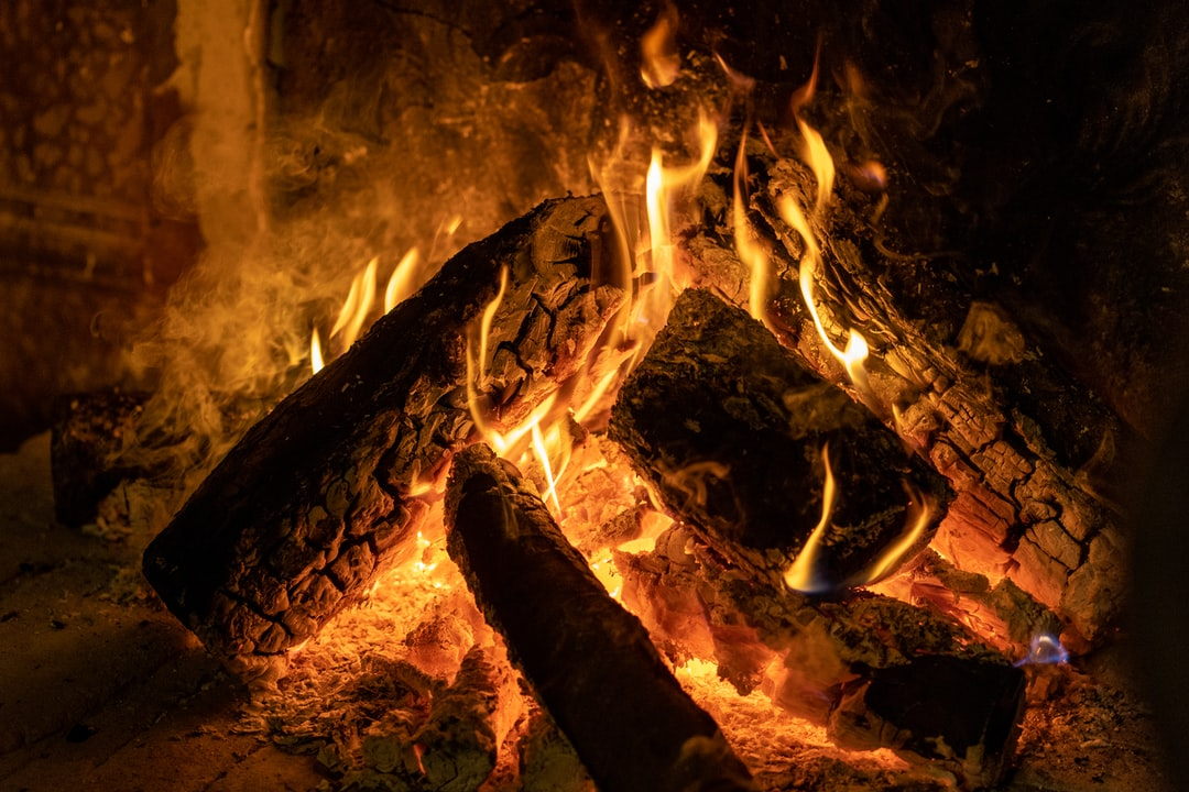 A Cozy Wood Fire Burns Bright In An Old Fashioned Fireplace - unsplash