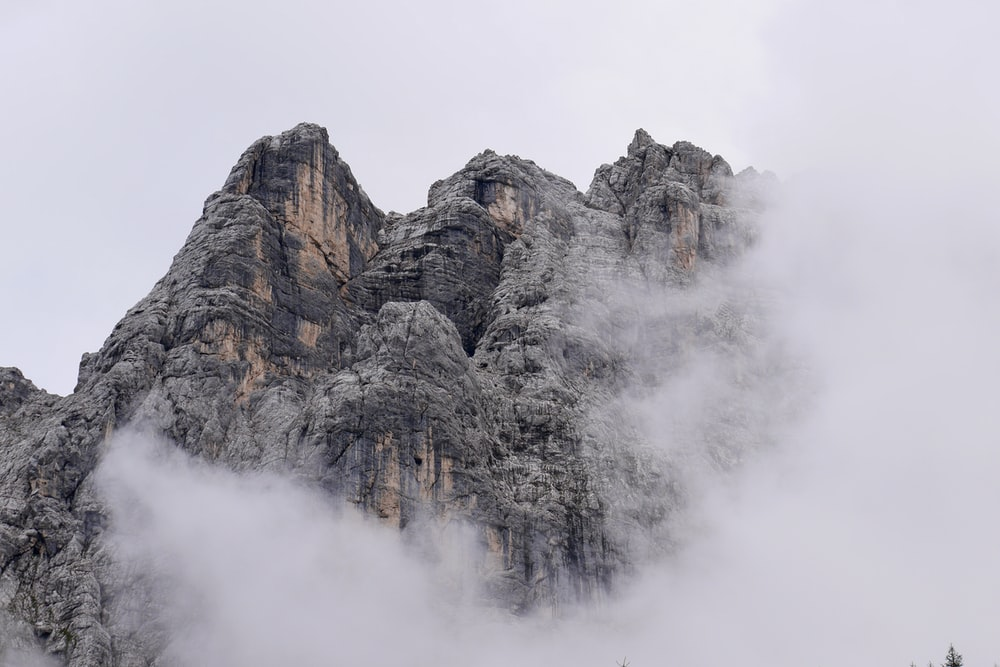 gray rocky mountain covered with white clouds