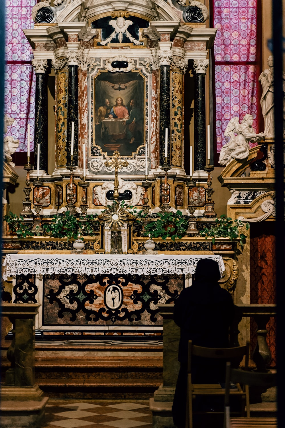 person in black robe standing in front of gold and black cathedral