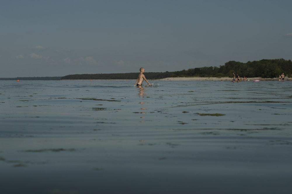 woman in white bikini walking on beach during daytime