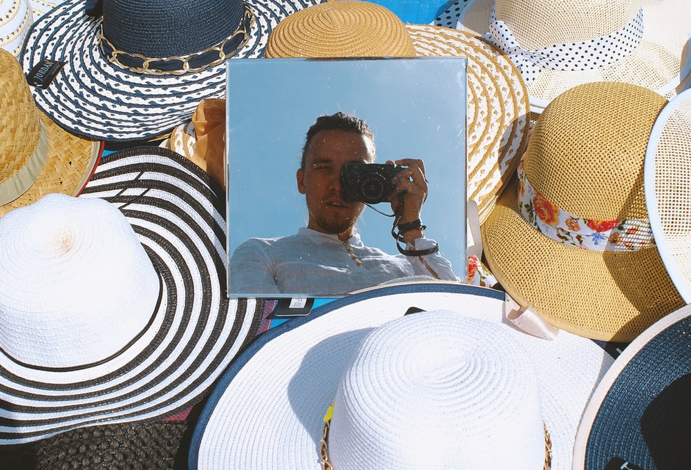 woman in black and white stripe shirt and brown sun hat