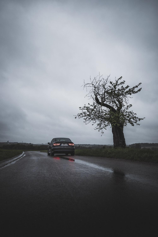black suv on road under gray sky