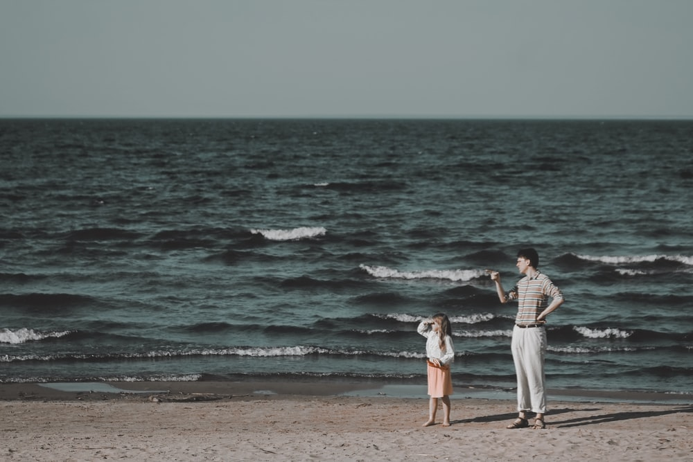 man and woman standing on beach during daytime