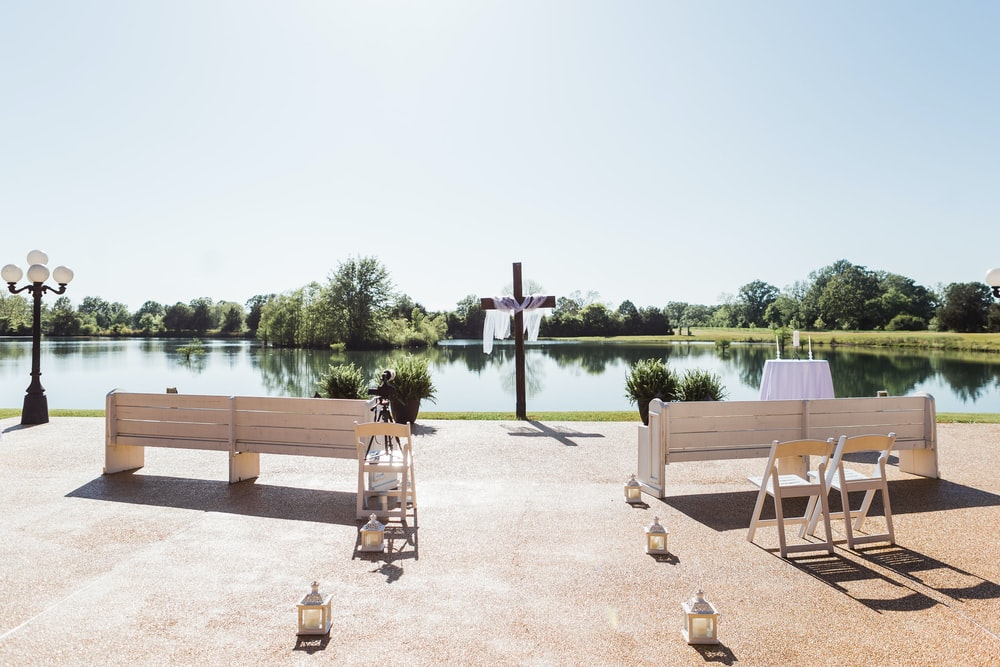 brown wooden picnic table near body of water during daytime