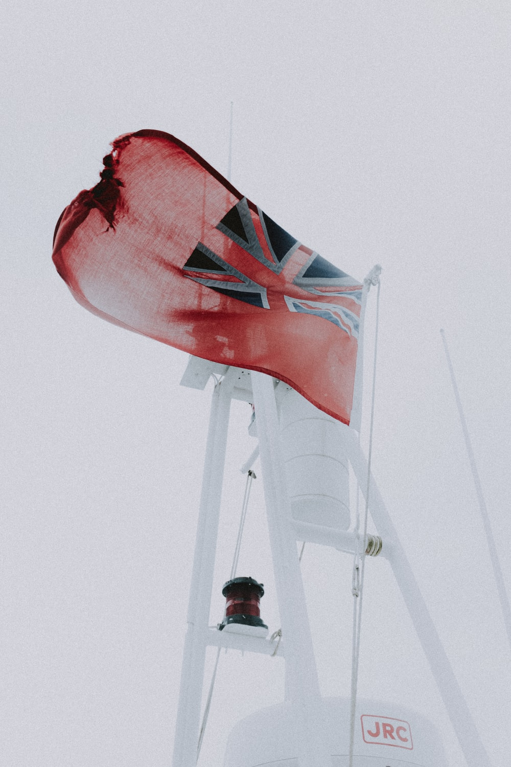 red and white flag on white metal pole