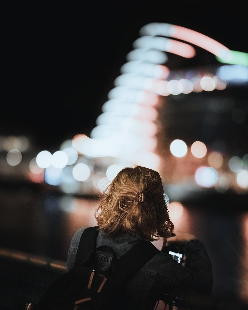 woman in black jacket standing on sidewalk during night time