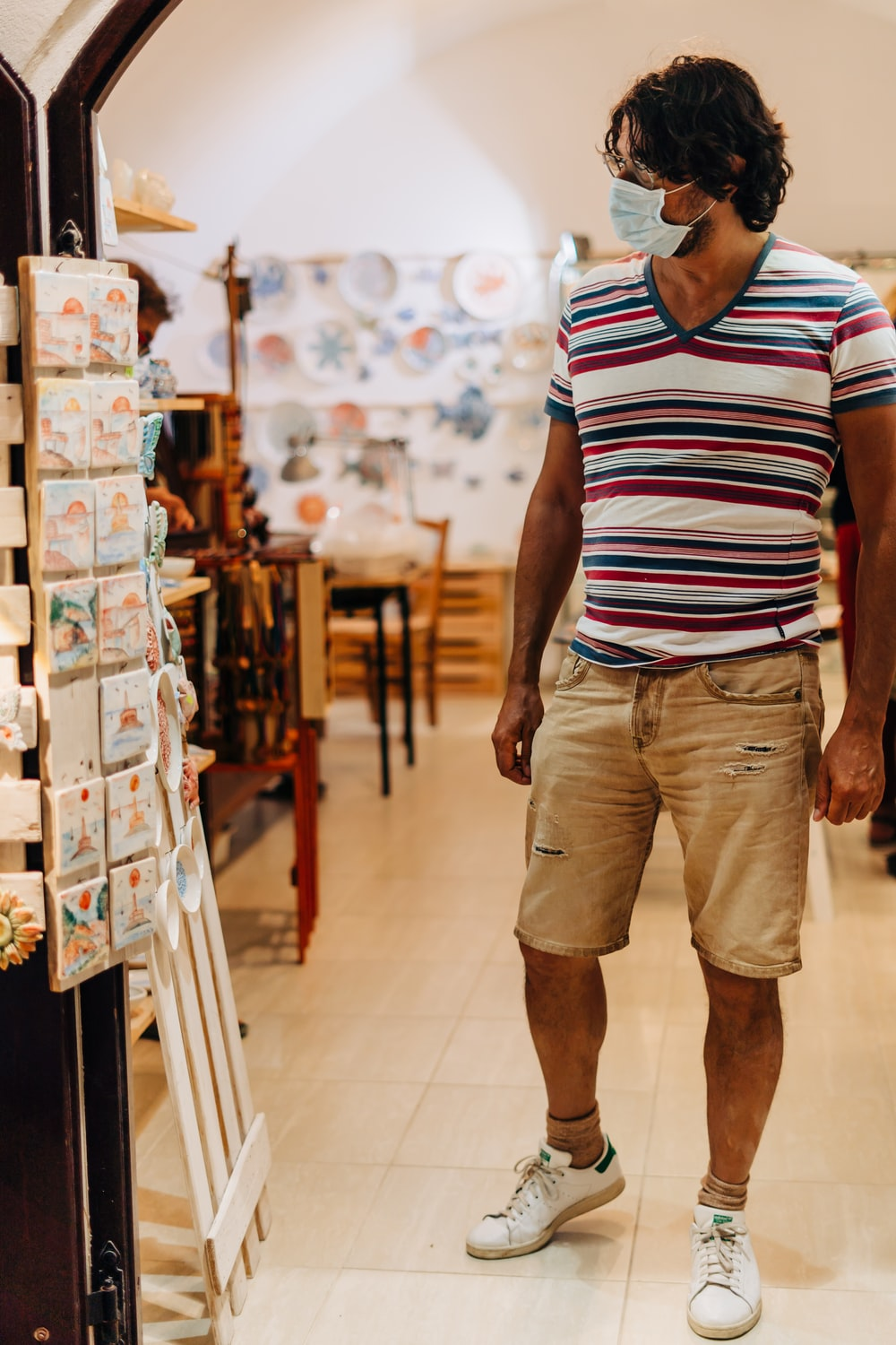 man in white red and blue striped polo shirt and brown cargo shorts standing
