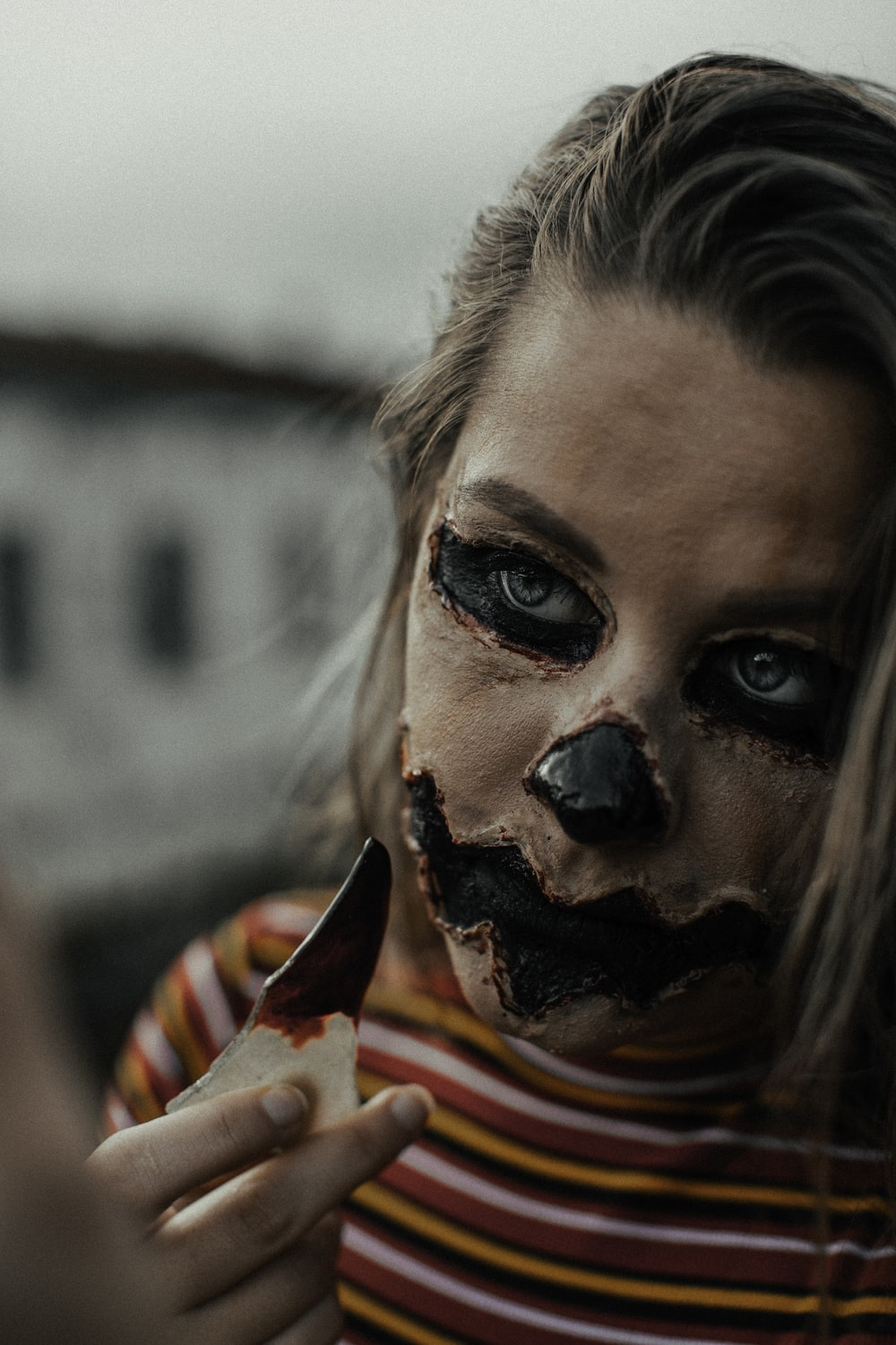 woman in red and yellow shirt with black and white face paint