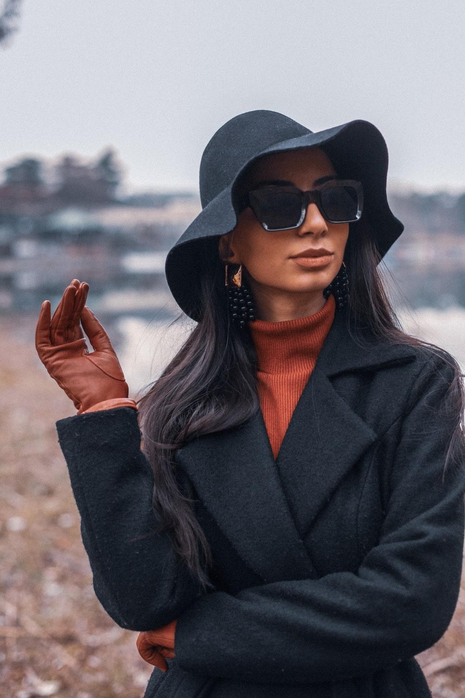 woman in black coat wearing black sunglasses and black hat